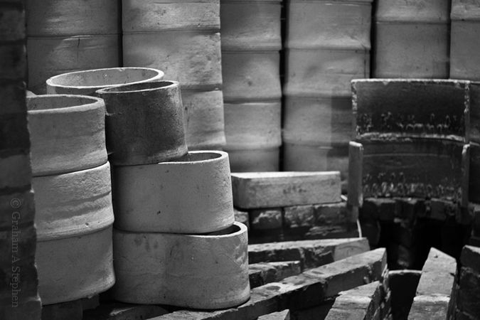 Saggars stacked in the kiln.  Saggars were the rough clay containers into which the china pieces were placed to protect them from smoke in the kiln.  Hot air was channelled under the kiln floor and up through the saggars.  Bone china items received an initial, or biscuit, firing at a temperature of 1230ºC and received a second firing after glazing to make the clay impervious to fluids.  Decorated items were fired several times at different temperatures to obtain a full range of colours.